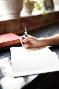 person writing in journal dealing with stress no alcohol