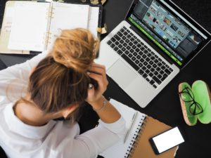 woman with head in hands at work, hungover and unproductive