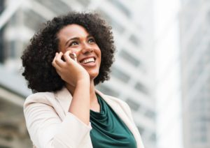 woman happy and smiling, on the phone to colleague