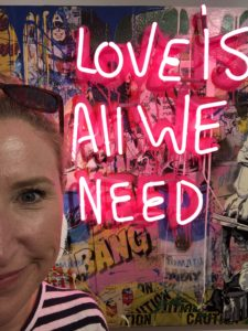 "neon sign saying ""love is all we need"""