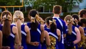 community cheering people on, cheerleaders standing in a row